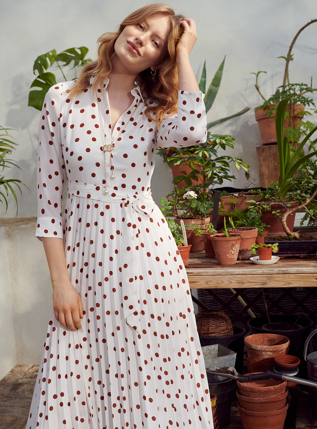 Model wearing a polka dot dress stands in front of potted plants.
