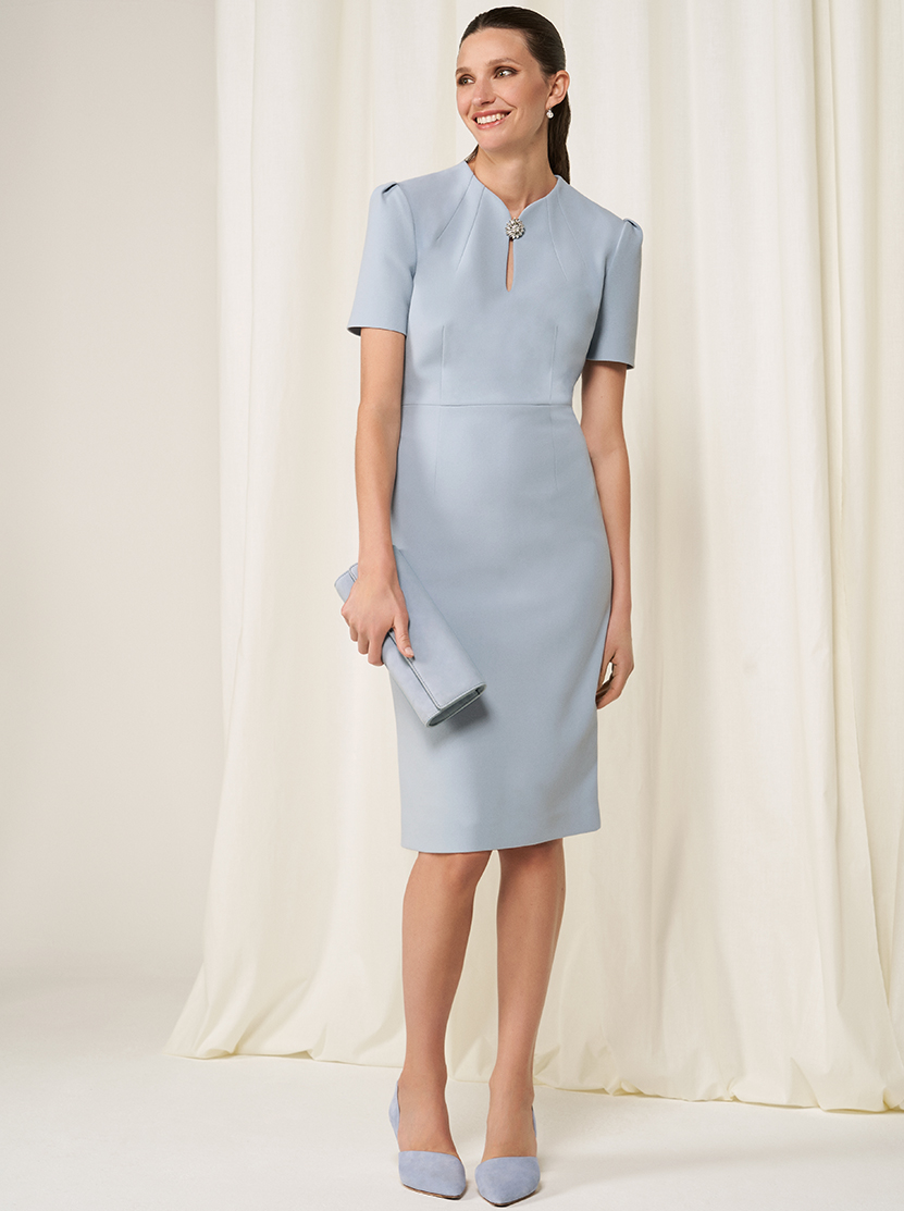 Model wears a brooch embellished shift dress with heels and a clutch bag.