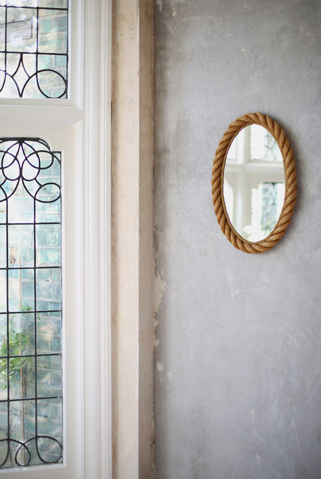 A mid century rope mirror reflects the light in Hannah's home.