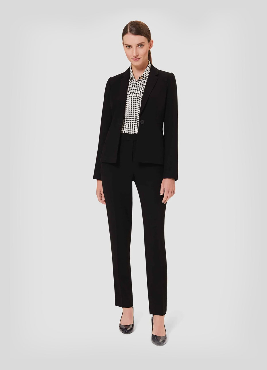 Women's trouser suit for work worn with a dogtooth patterned shirt and black court shoes by Hobbs.