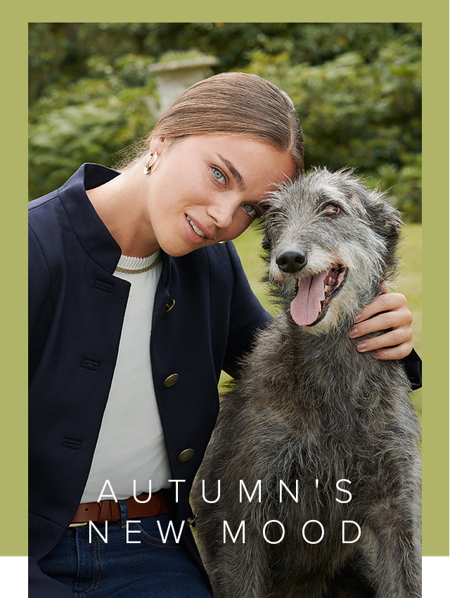Model poses in a blue blazer next to a dog