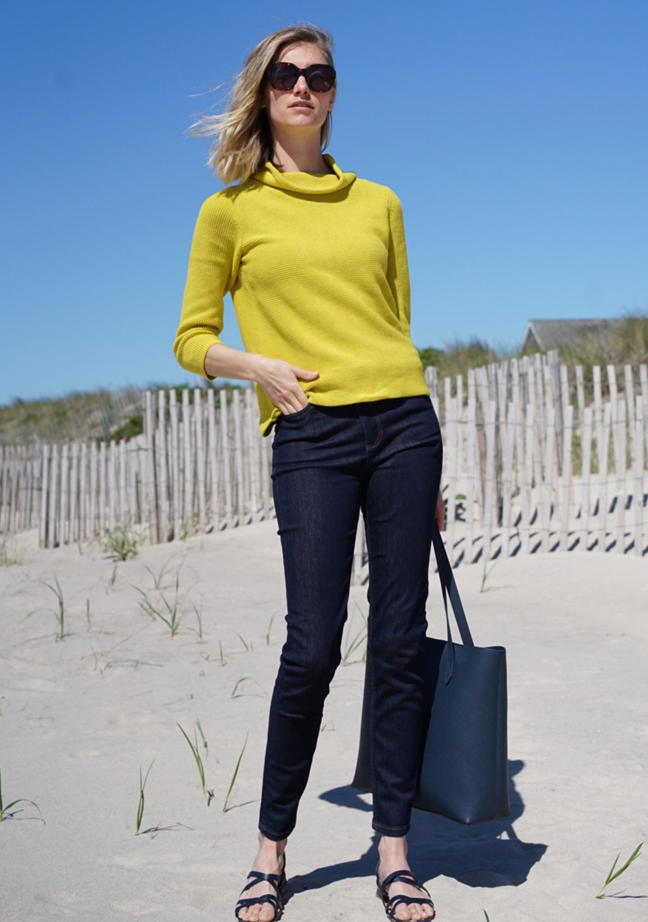 A blonde woman stands on a beach in a yellow roll neck jumper with dark denim jeans, sandals and a navy blue leather tote bags