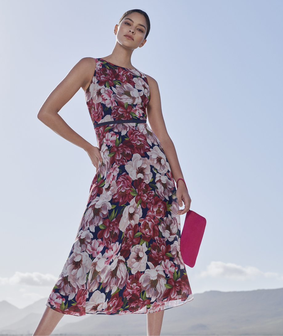 Floral midi dress paired with a pink clutch by Hobbs.