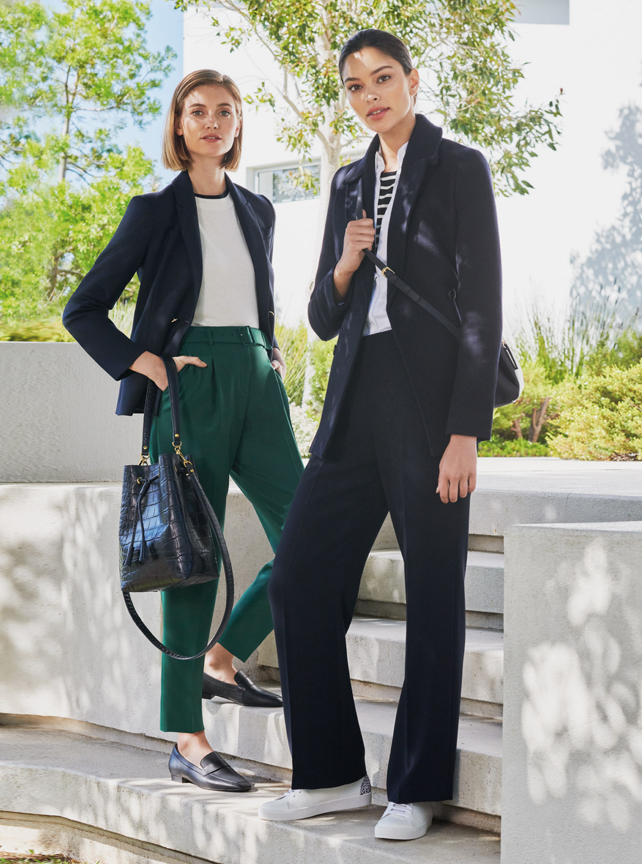 Women's trouser suit outfits, the outfit on the left pairs the suit with a white top, green tailored trousers, black loafers and a black leather tote bag. The outfit on the right pairs the suit with a stripey top, a black crossbody bag, wide leg trousers and white trainers, all from Hobbs.