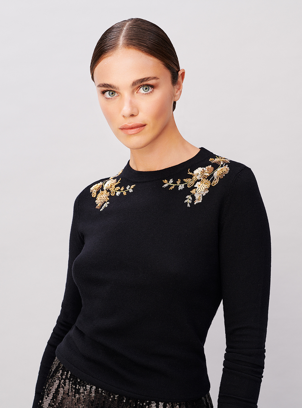 A bead embellished jumper worn with a sequin midi skirt from Hobbs.