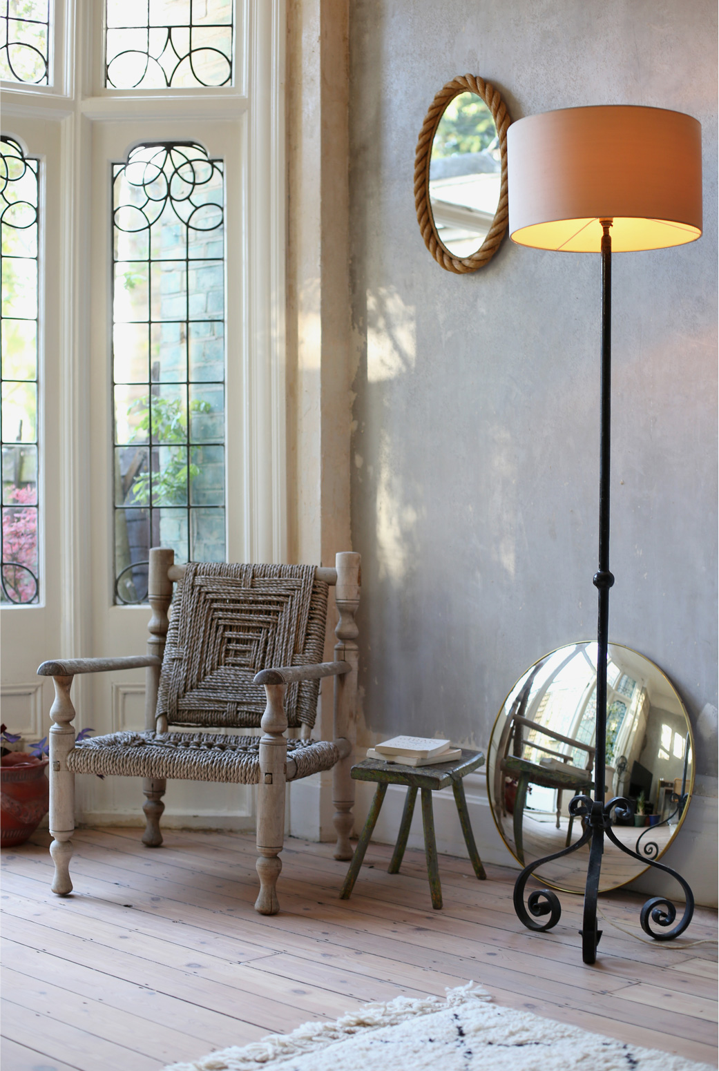 Bring the outside in, beautiful leaded windows in Hannah's flat featuring a mid-cenury rope chair and a wrought iron table lamp.