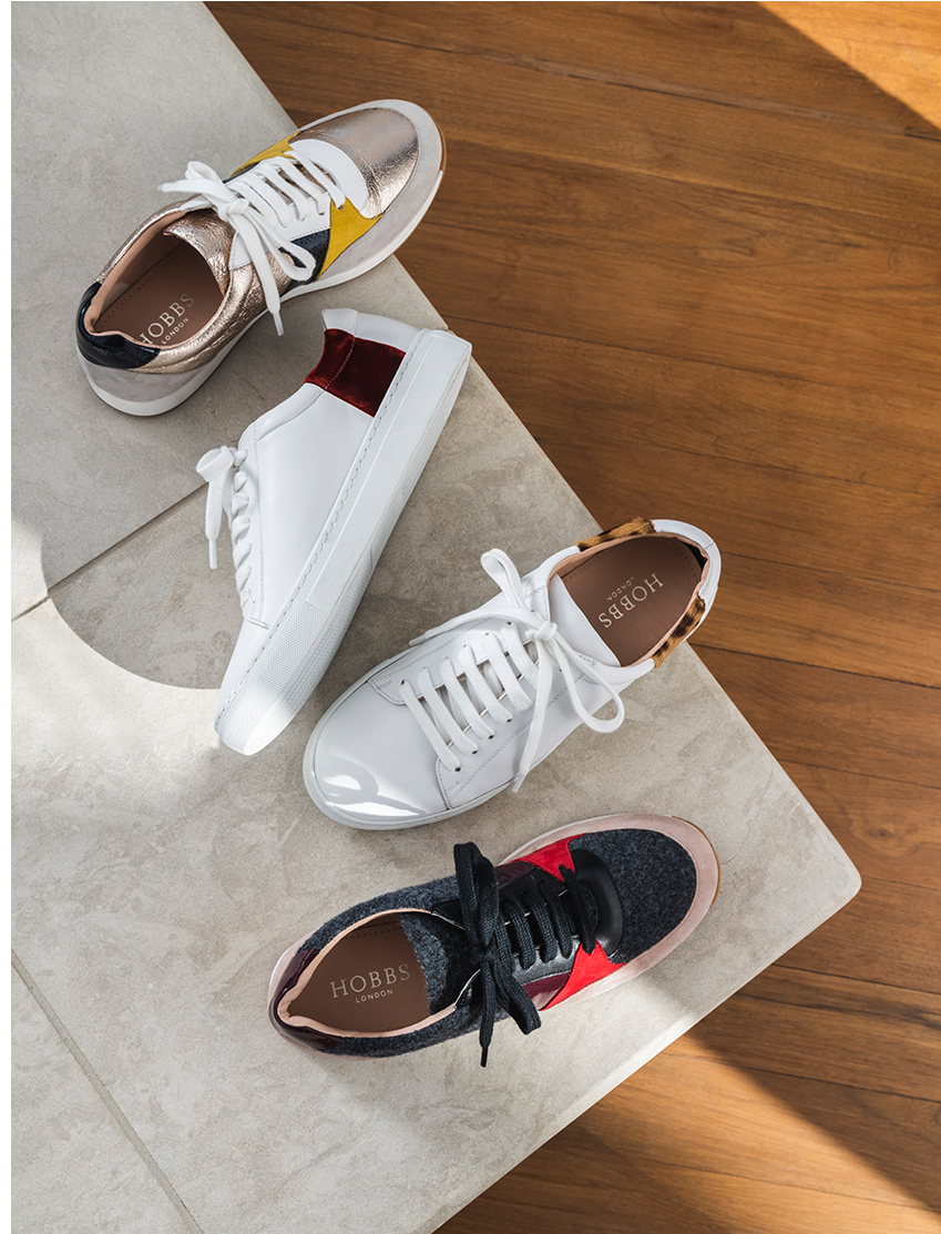 a selection of white leather and colourful trainers