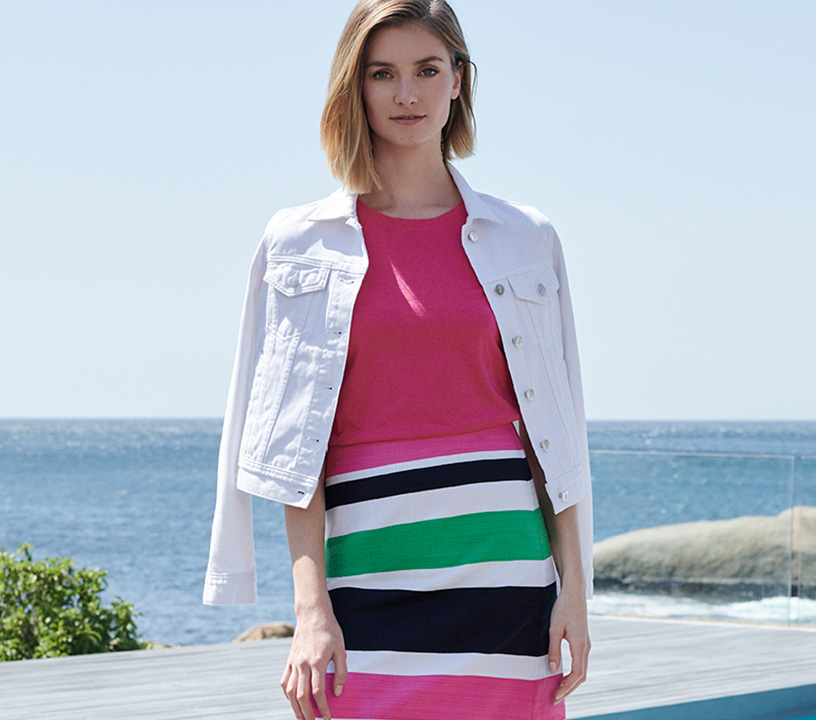 White denim jacket over pink top and striped skirt