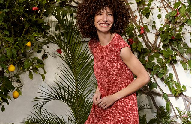 Model wearing a Hobbs red print dress in a garden.