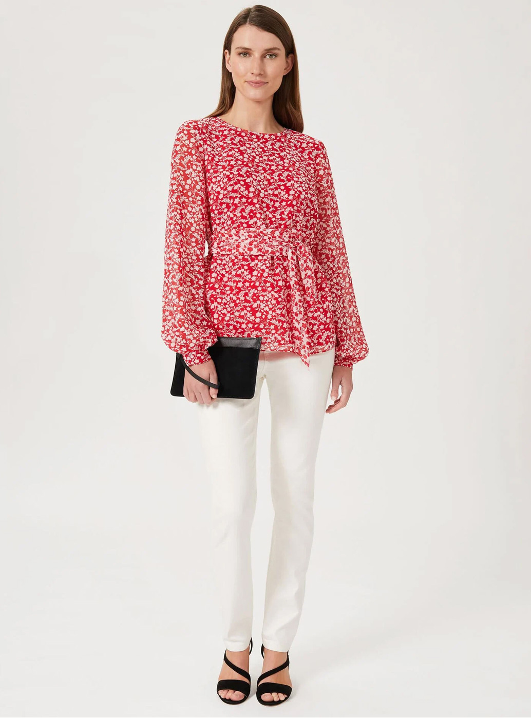 Model wears a floral print blouse and white jeans with heels and a clutch.