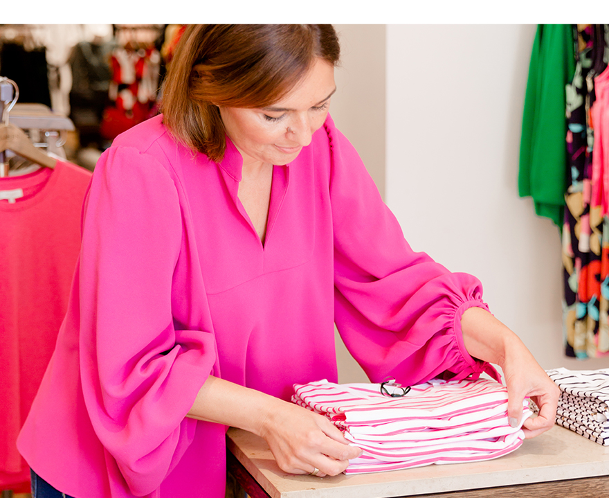 Hobbs UK & International Visual Specialist, Selena Trkuljia, photographed wearing a pink blouse while folding up garments in-store.