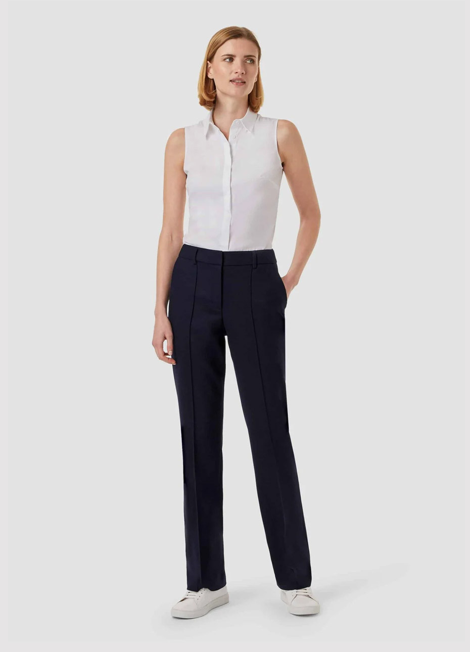 Sleeveless work blouse in white worn with black straight leg trousers and white trainers from Hobbs.