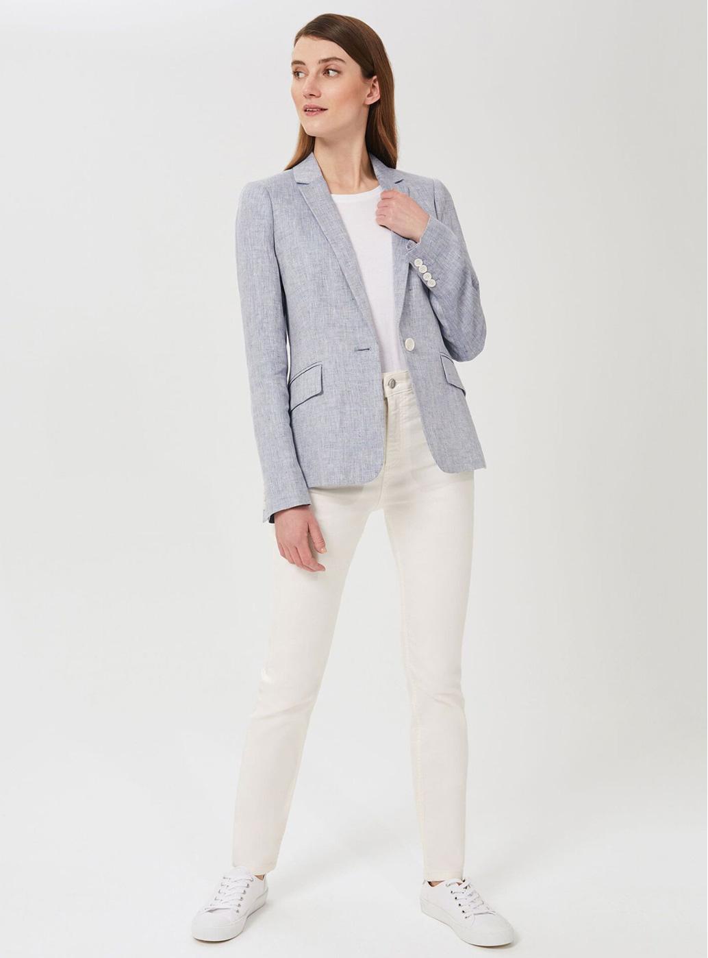 Model wears white jeans and a blue linen blazer.