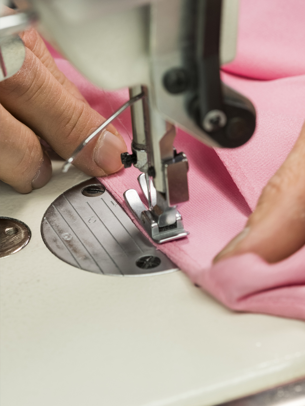Sewing machine stitching pink fabric