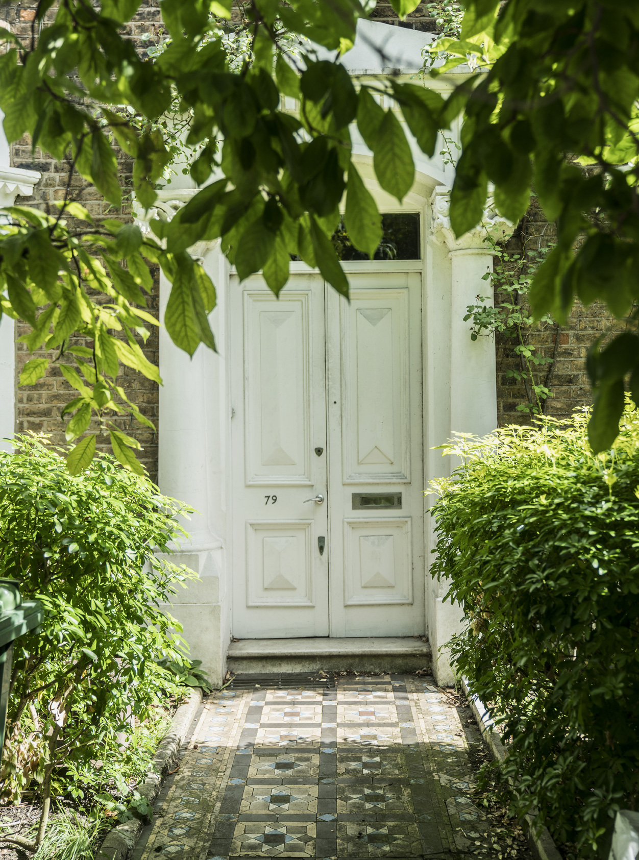 An effortlessly chic white classic London double front door with Victorian tiled path.