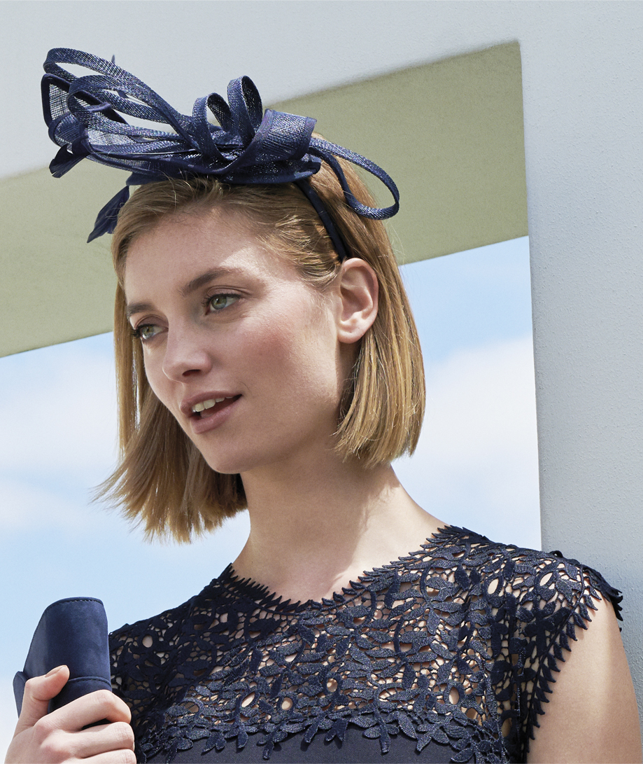 A navy fascinator to go with occasionwear such as a mother of the bride dress by Hobbs.