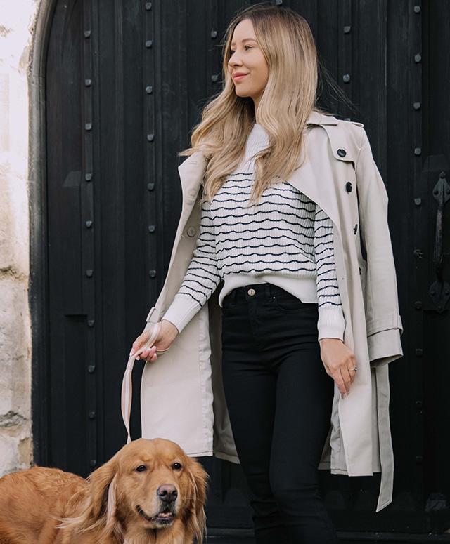 Fashion blogger @shegoeswear photographed on a walk wearing Hobbs Saskia neutral trench, Daniella jumper and Gia black jeans.