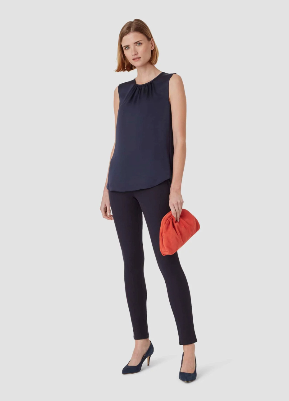 Dark navy top worn with black denim jeans, black court shoes and a red clutch bag by Hobbs.