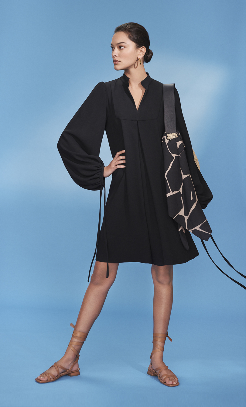 Model poses in a short black dress with blouson sleeves