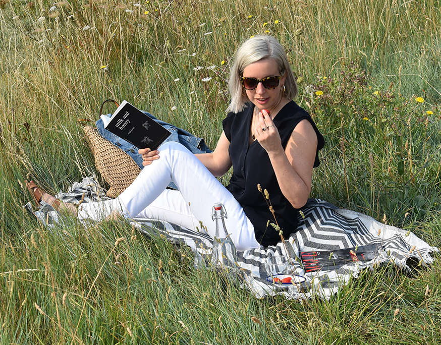 Jen Wilkins, Creative Copy & Editorial Manager at Hobbs enjoys a picnic with some strawberries in a secluded spot by the coast while reading a book.