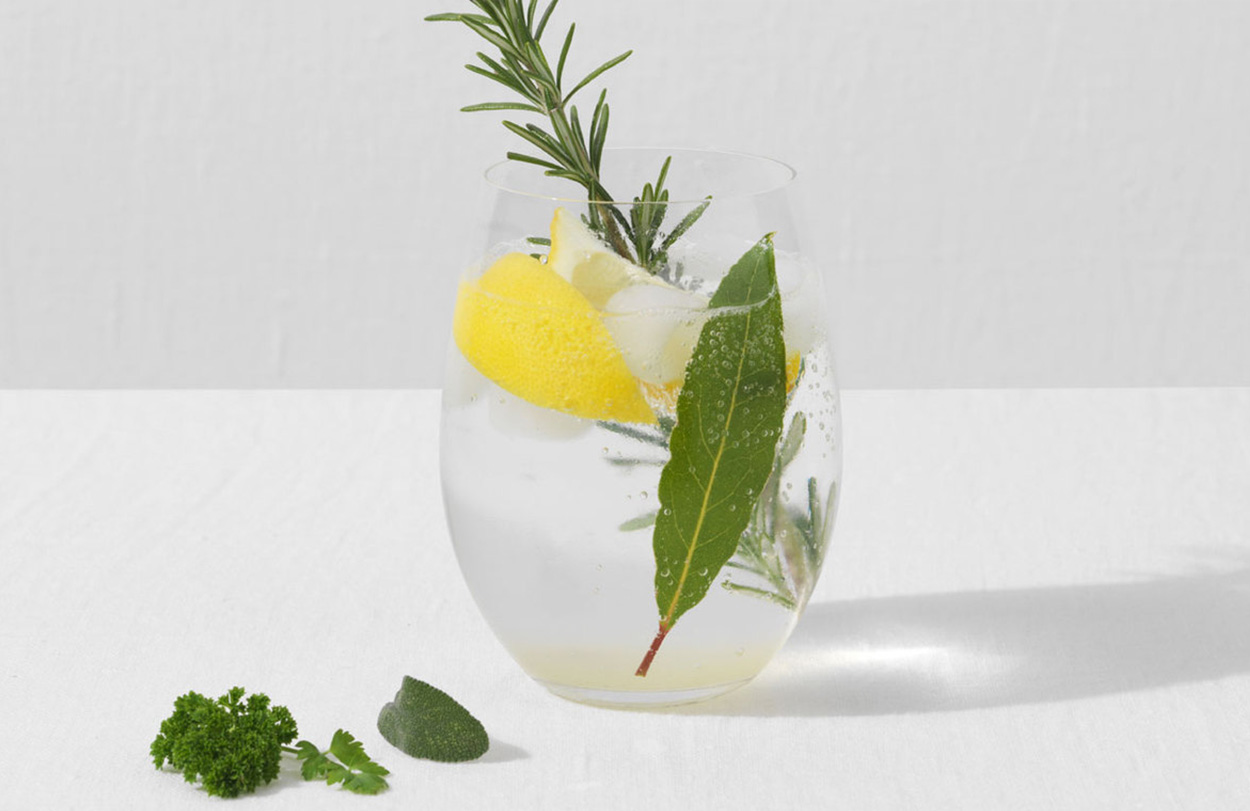 Glass containing refreshing Gin Fizz Cocktail with Lemon and Rosemary