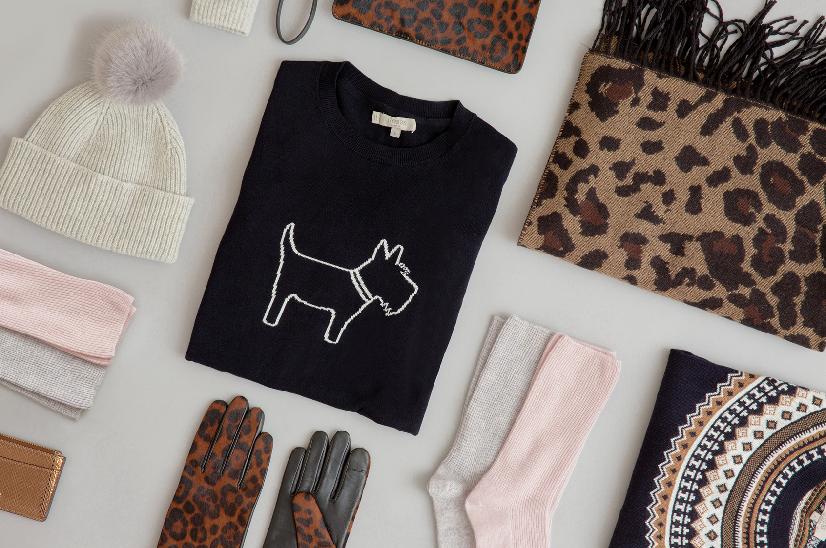 A selection of Christmas gifts including a novelty knit, leopard print scarf and gloves.