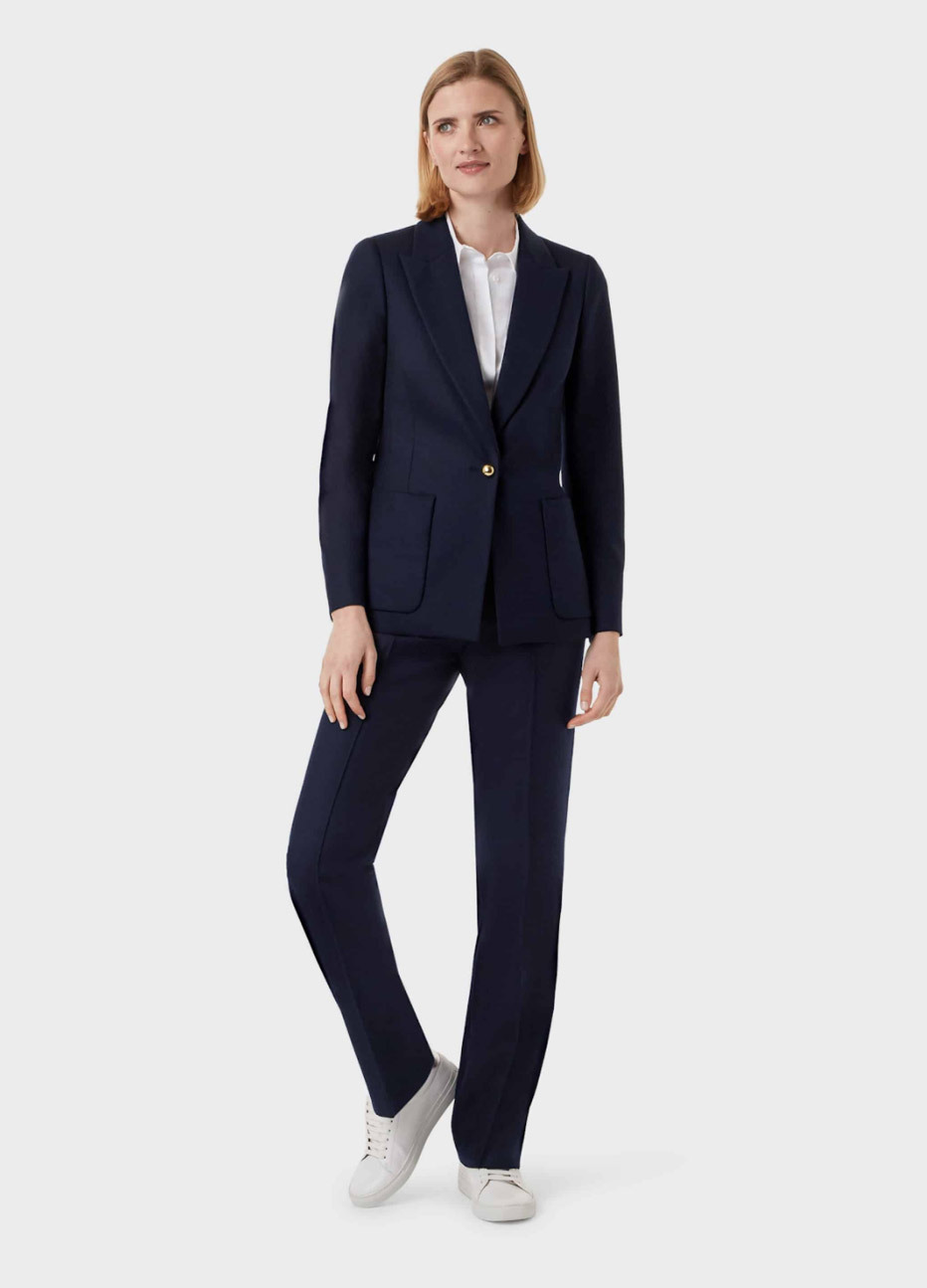 Women's blazer in black worn with matching work trousers in black, with a white blouse underneath and white trainers, by Hobbs.