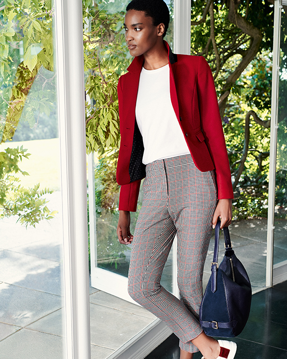 Model wears a bright red wool jacket, tailored trousers, white leather trainers with a blue leather bag