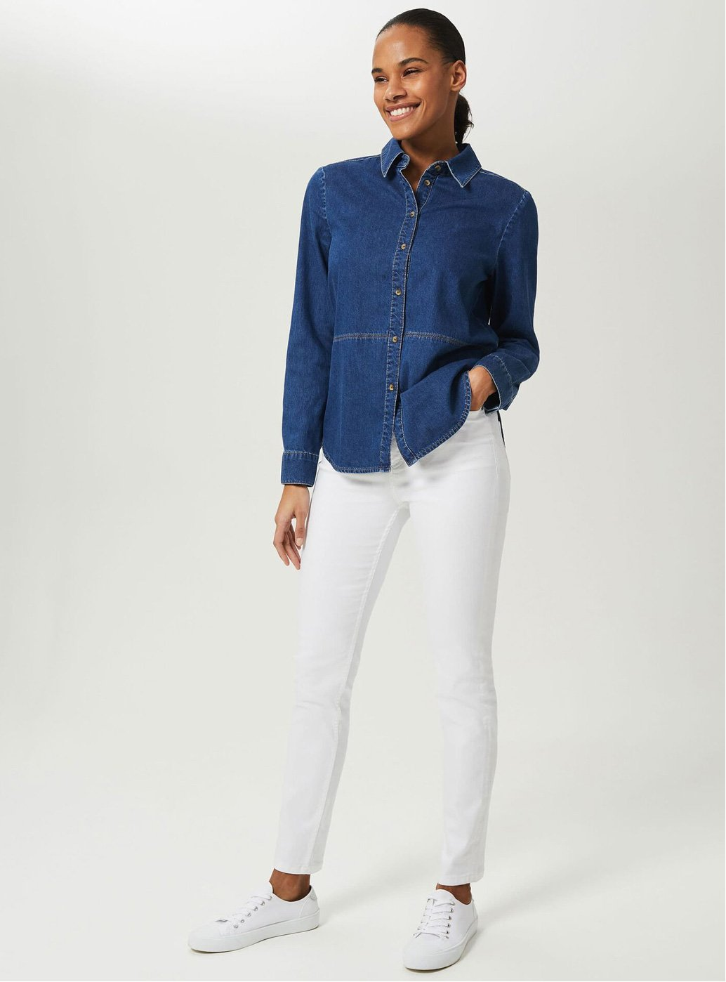 Model wears a blue denim shirt, white jeans and trainers.