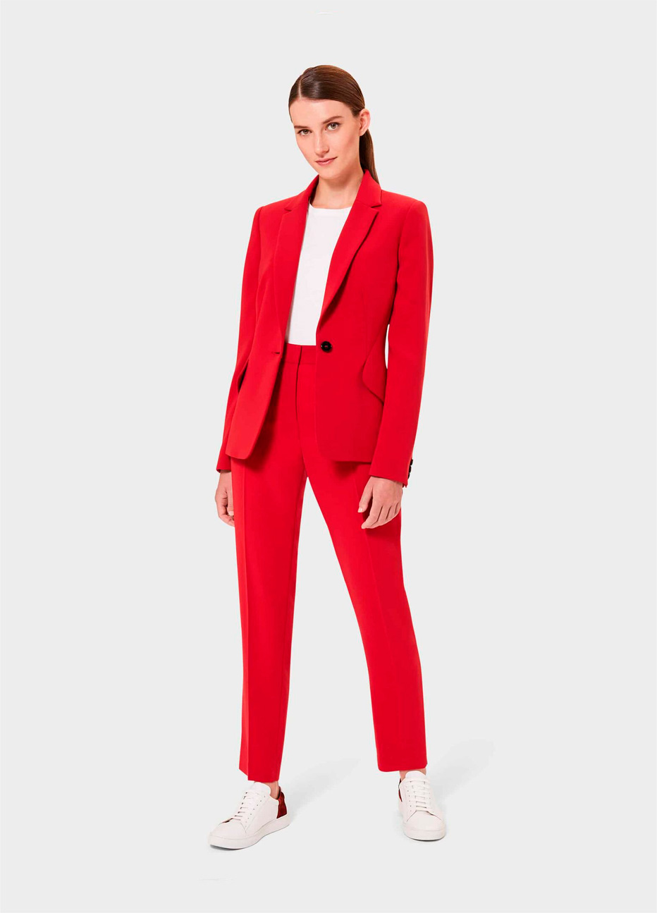 Women's trouser suit in red styled with a white top and white trainers by Hobbs.