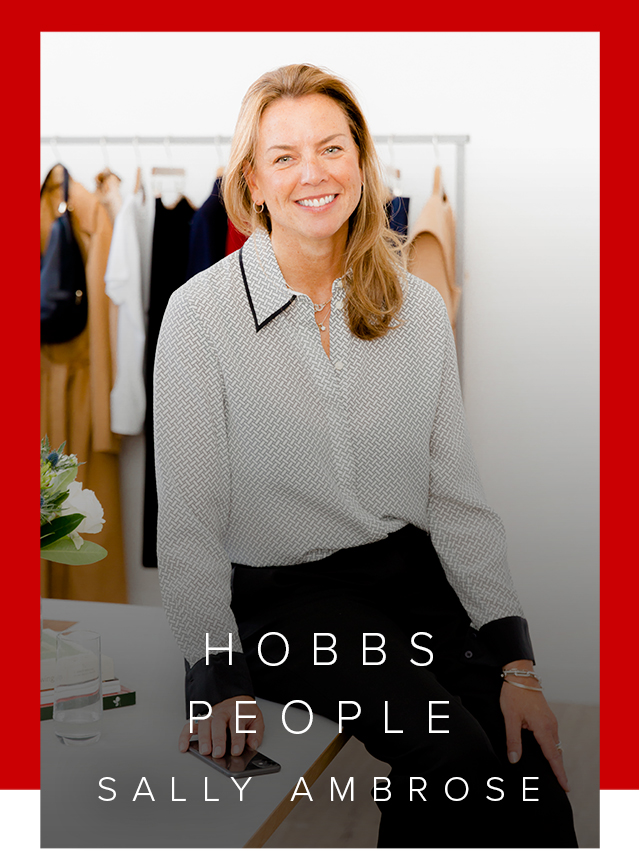 Hobbs' Product Director, Sally Ambrose, photographed wearing a silk shirt while leaning on an office desk.