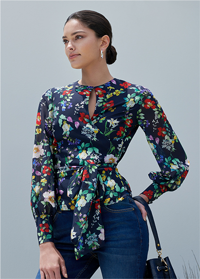 Woman poses in a navy blue floral wrap top styled with jeans and a navy blue leather hand bag