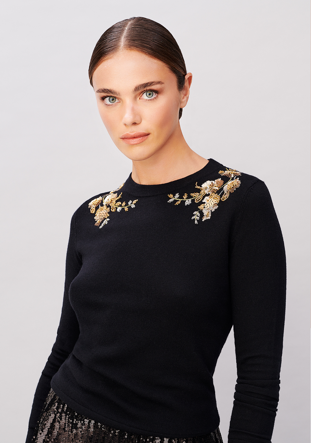Close-up image of model wearing a black jumper with a gold embellished neckline.