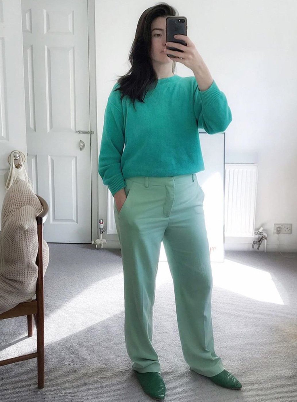 Brand stylist Maddy Moxham takes a selfie  dressed in a serene green outfit at home