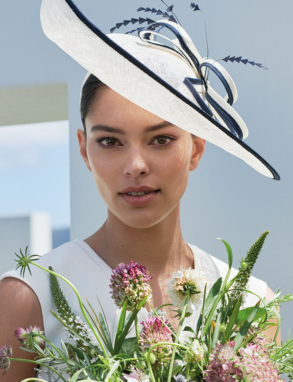 Model wearing ivory and navu fascinator and holding flowers