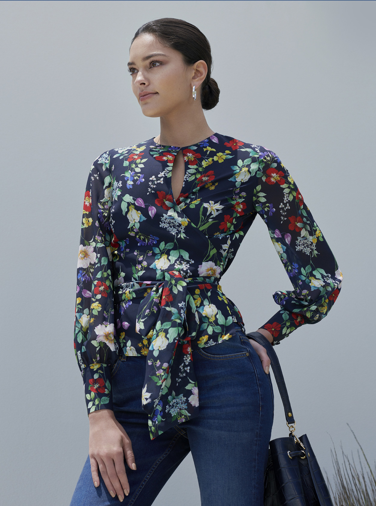 Floral blouse with waist tie detail paired with blue jeans and leather bucket bag by Hobbs.