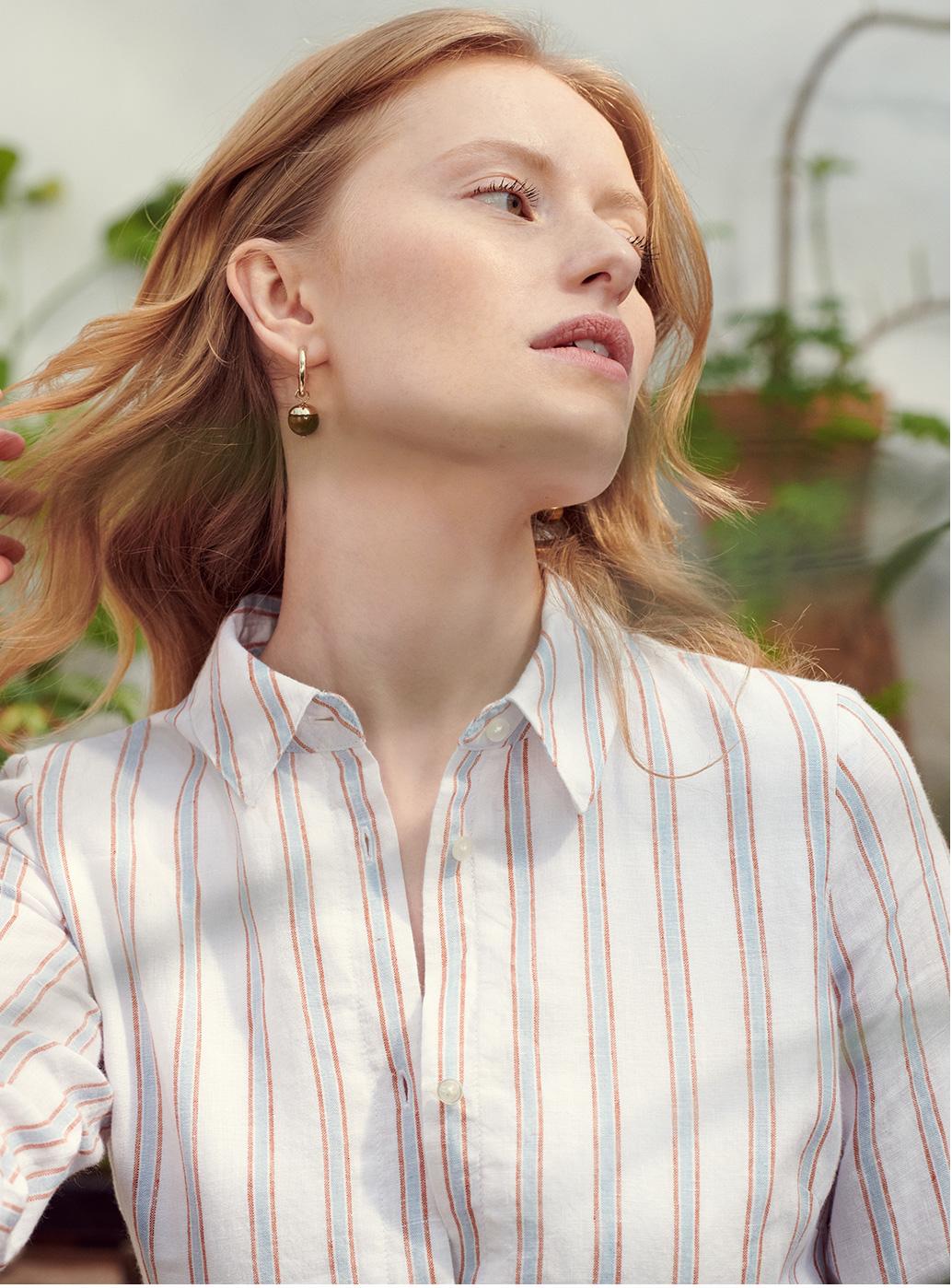 Model in a striped shirt dress wears a pair of earrings.