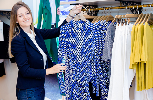 A Hobbs stylist holding up a blue shirt dress on a hanger in-store, white denim jeans and yellow tshirts hang in the background.