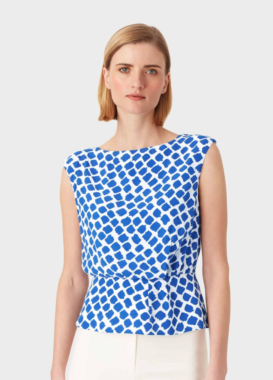 Women's top in blue and white with a contemporary spot print styled with white trousers, by Hobbs.