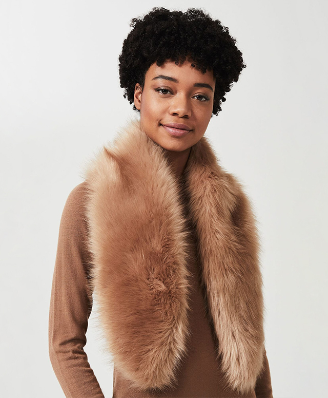 Model photgraphed wearing a beige faux fur wrap scarf over a camel roll neck jumper.