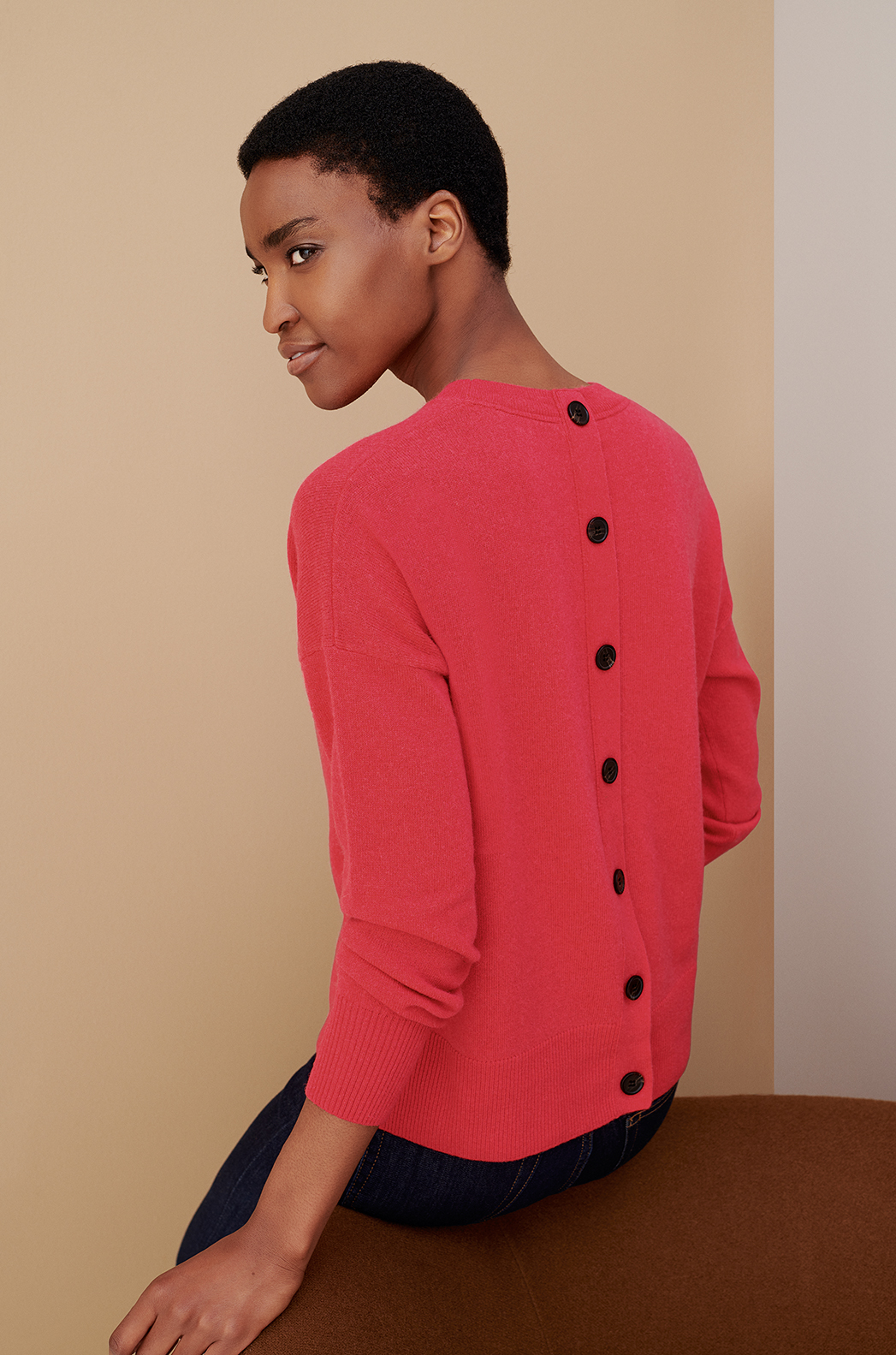 Model wears a bright jumper with button detailing from Hobbs.