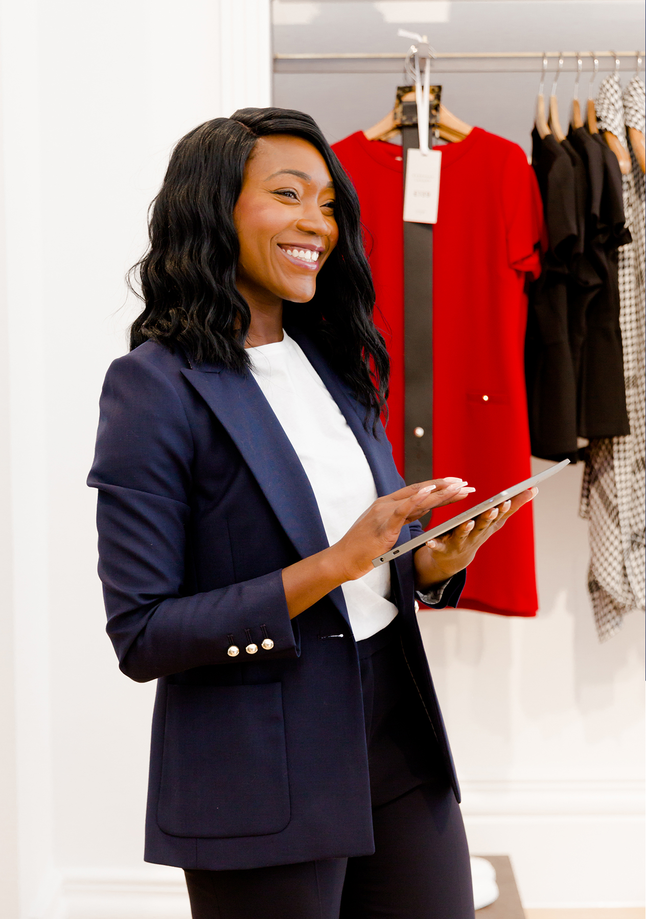 Store Manager, Tayo Olode-Okuta, photographed holding a digital tablet in the St. Paul's store.