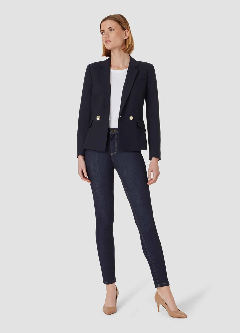 Women's blazer in black paired with a white top underneath, black jeans and nude court shoes by Hobbs.