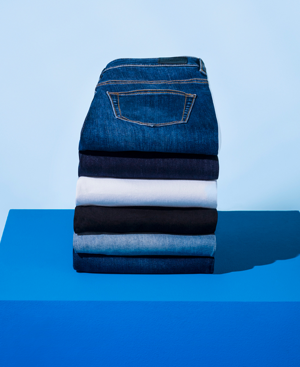 A stack of different shade of denim sit on a blue plinth