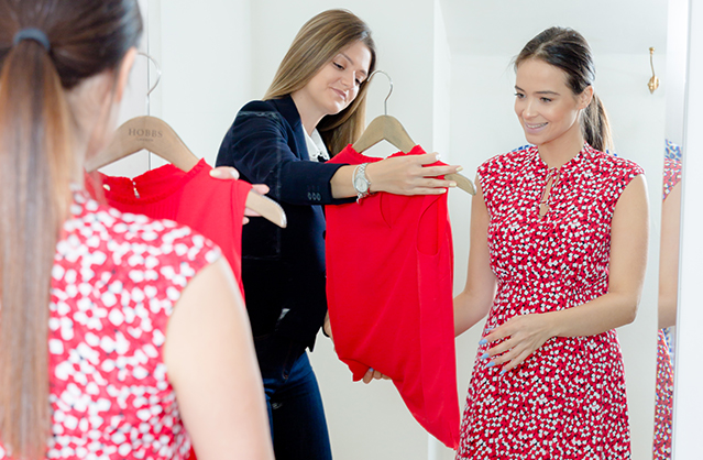 A Hobbs stylist, wearing a dark navy blazer, dark blue jeans and a watch holds up a red blouse on a hanger to show a customer, wearing a red floral dress, during a one-to-one personal styling appointment in-store.