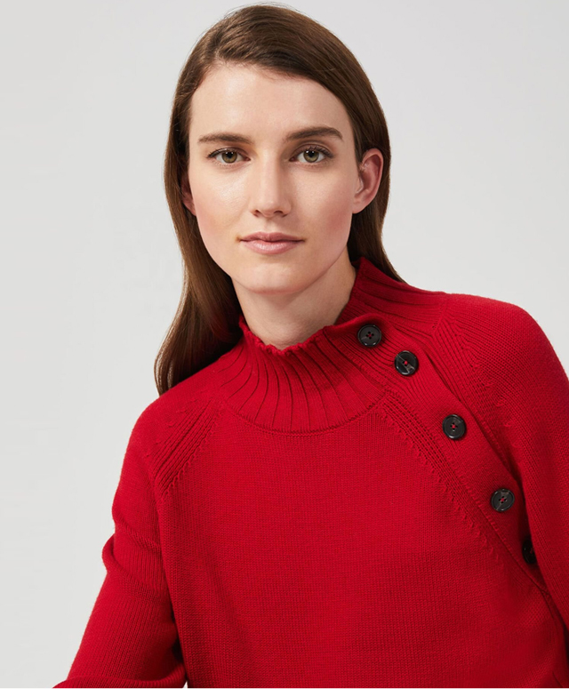 Model photographed wearing a red sweater with button detailing.