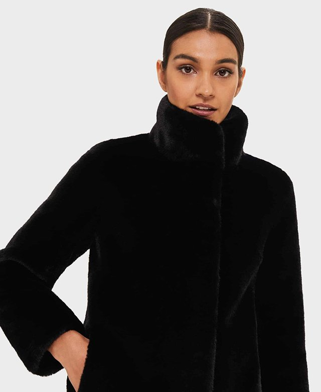 Model photographed wearing a buttoned up navy faux fur coat with funnel neckline.