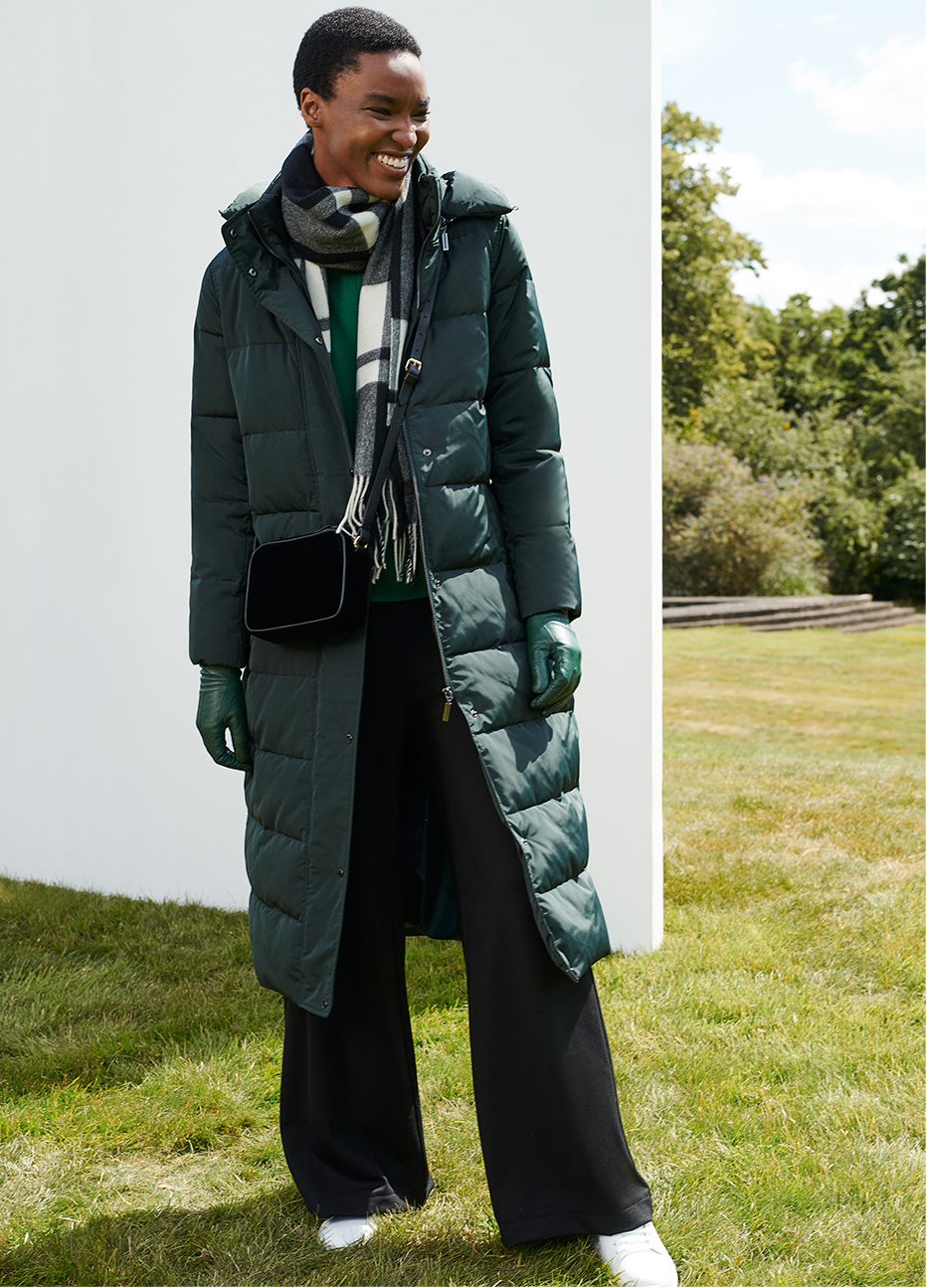 Full length image of model wearing a puffer coat and checked scarf.