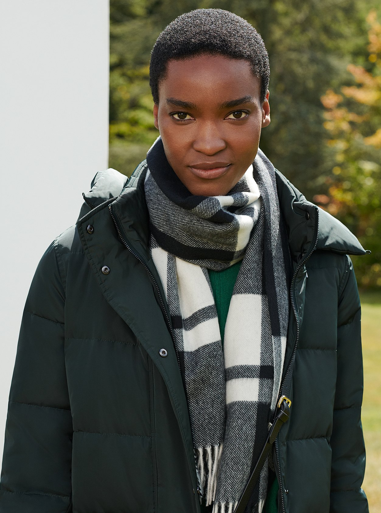 Close-up of model in a garden wearing a puffer coat and checked scarf.