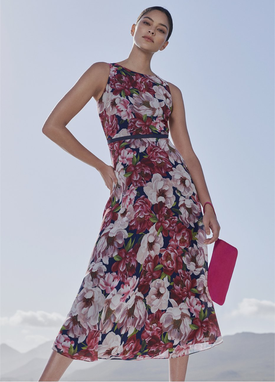 Midi-length occasion dress with a pink floral pattern paired with a pink wristlet clutch and flat shoes by Hobbs.